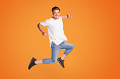 istock Happy handsome man jumping with big smile. 1006573902