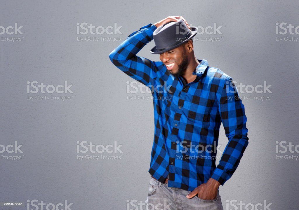 happy handsome man laughing with hand to hat stock photo