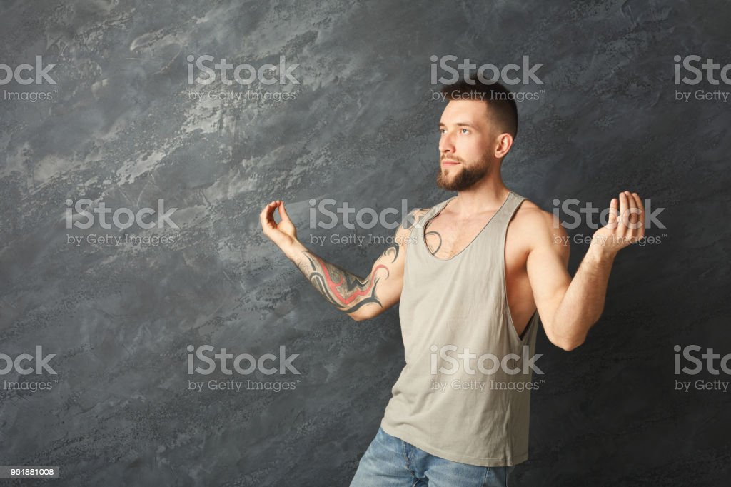 Happy handsome man making a yoga pose in studio royalty-free stock photo