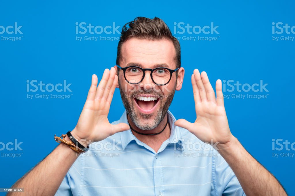 Happy handsome man screaming against blue background Summer portrait of handsome man wearing blue shirt and glasses, screaming. Studio shot, blue background. 30-39 Years Stock Photo