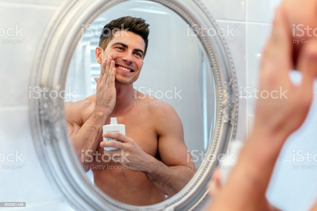 Happy handsome man shaving in bathroom stock photo