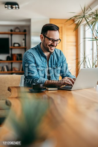 Happy handsome man using laptop at wooden table, portrait.