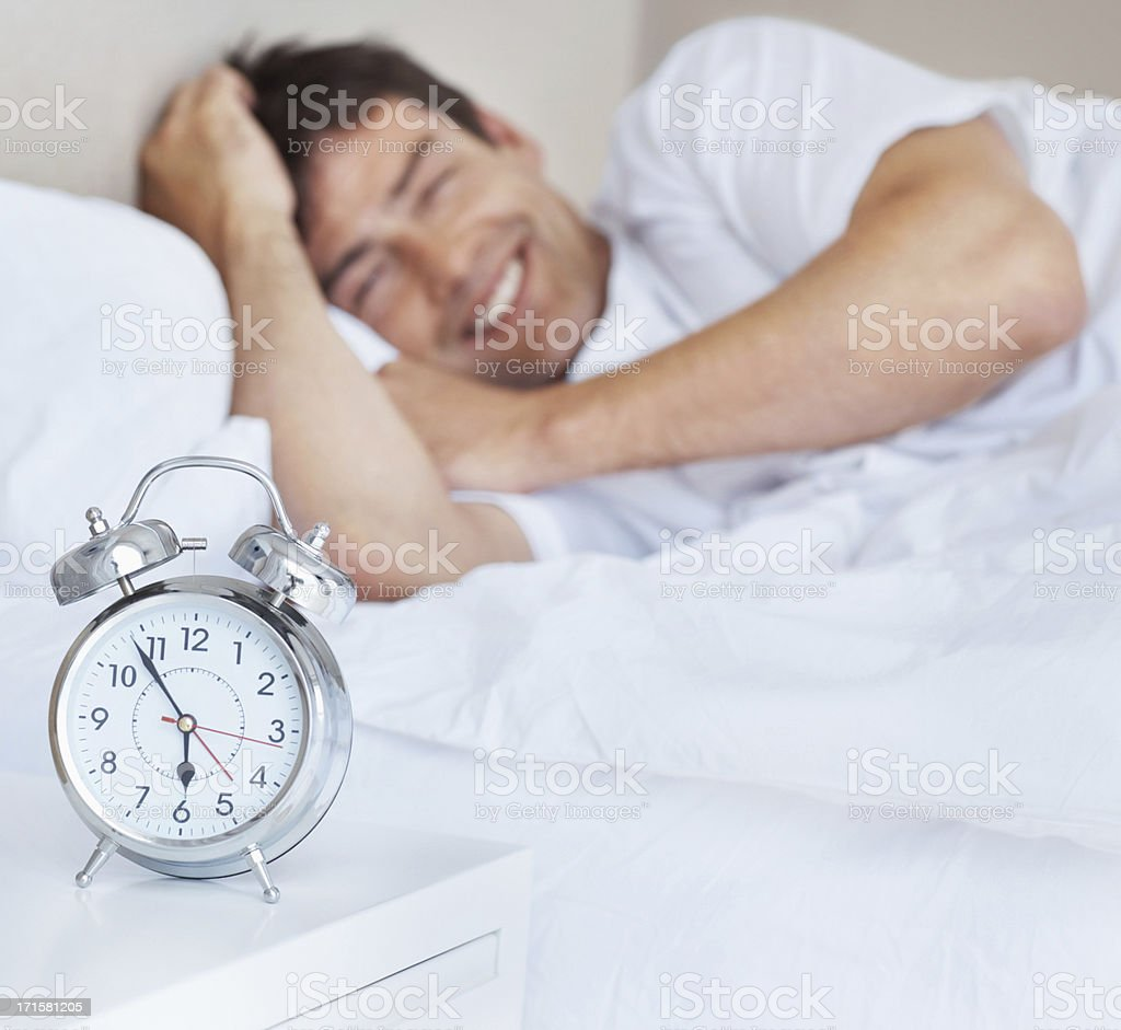 Happy handsome man with an alarm clock in the foreground royalty-free stock photo