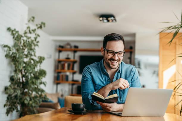 Feliz hombre guapo con computadora portátil y libreta de notas en la mesa de madera, retrato. - foto de stock