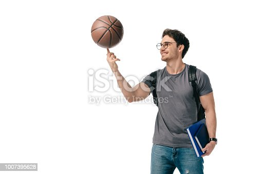 istock happy handsome student spinning basketball ball on finger isolated on white 1007395628