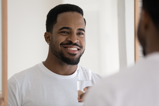Happy handsome stylish mixed race Black guy drinking pure fresh water at mirror in bathroom, holding glass, smiling at reflection, caring for aqua balance in morning, detox, healthy nutrition
