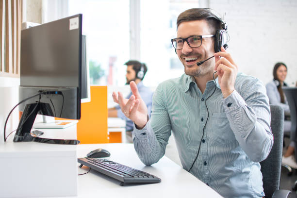 Happy handsome technical support operator with headset working in call centre stock photo