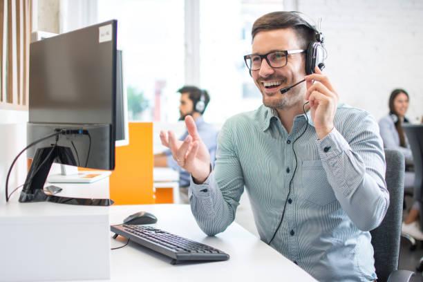 happy handsome technical support operator with headset working in call centre - coinvolgimento dei dipendenti foto e immagini stock