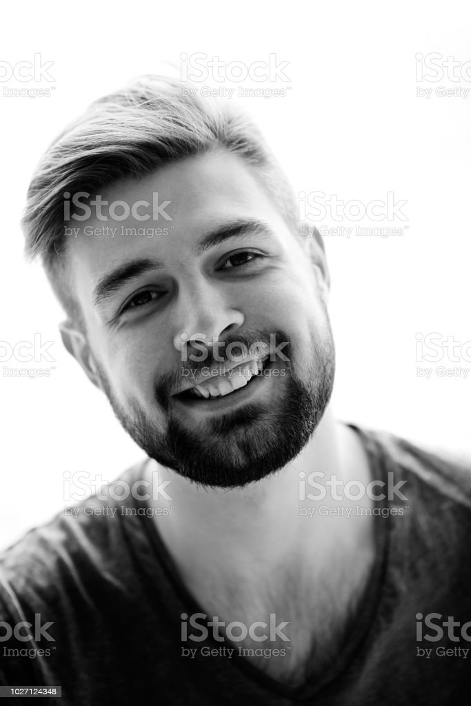 865656b8f4a Happy handsome young bearded man in V-shaped t-shirt smiling at camera against  white background