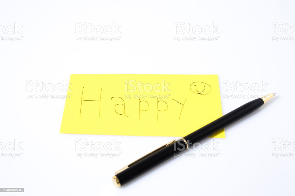 Happy handwrite with a pen and a smile on a yellow paper composition stock photo