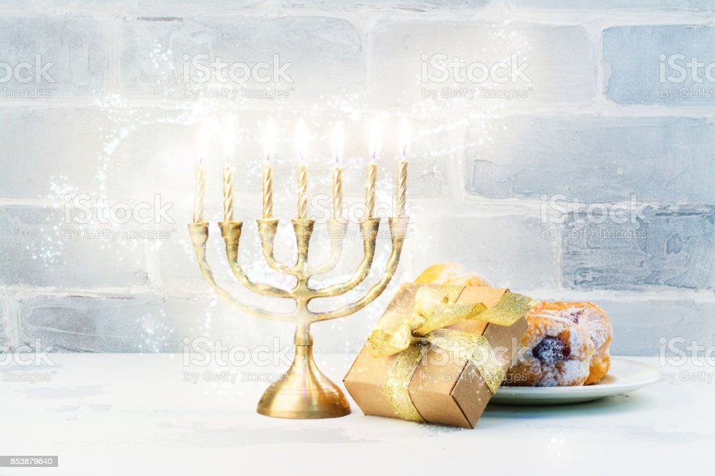 Happy Hanukkah background with menorah, burning candles and donu stock photo