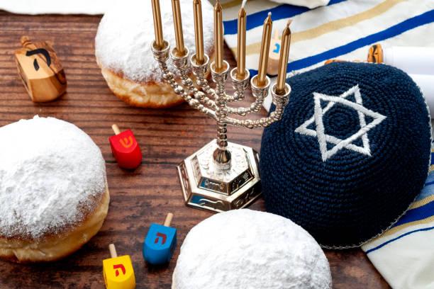Feliz Hanukkah - Dreidel (tapa giratoria de madera), menorah (vela tradicional), velas, tallit (chal de oración), kippa (sombrero religioso) y sufganiyot (rosquilla de jalea) sobre fondo de madera - foto de stock