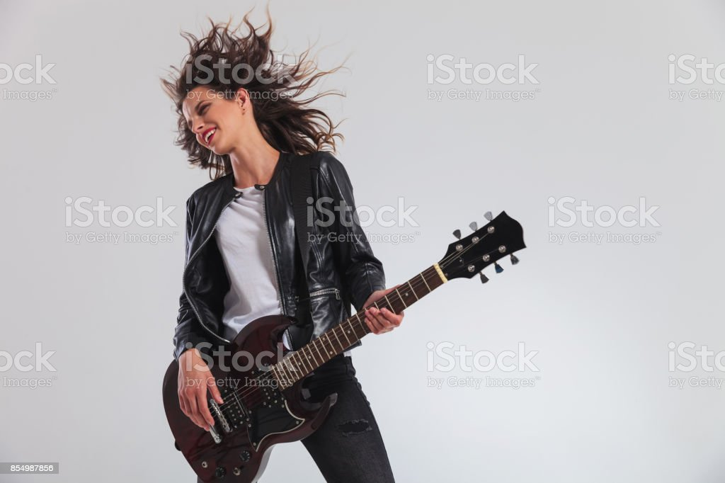 happy head banging woman guitarist playing guitar stock photo