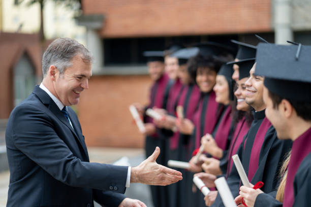 Happy headmaster giving a handshake to students on their graduation day Happy headmaster giving a handshake to students on their graduation day – education concepts college dean stock pictures, royalty-free photos & images