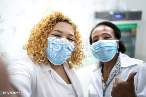 Happy healthcare coworkers taking a selfie at hospital