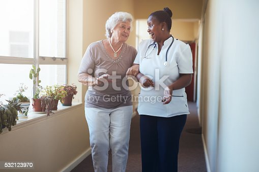 istock Happy healthcare worker walking and talking with senior woman 532123970