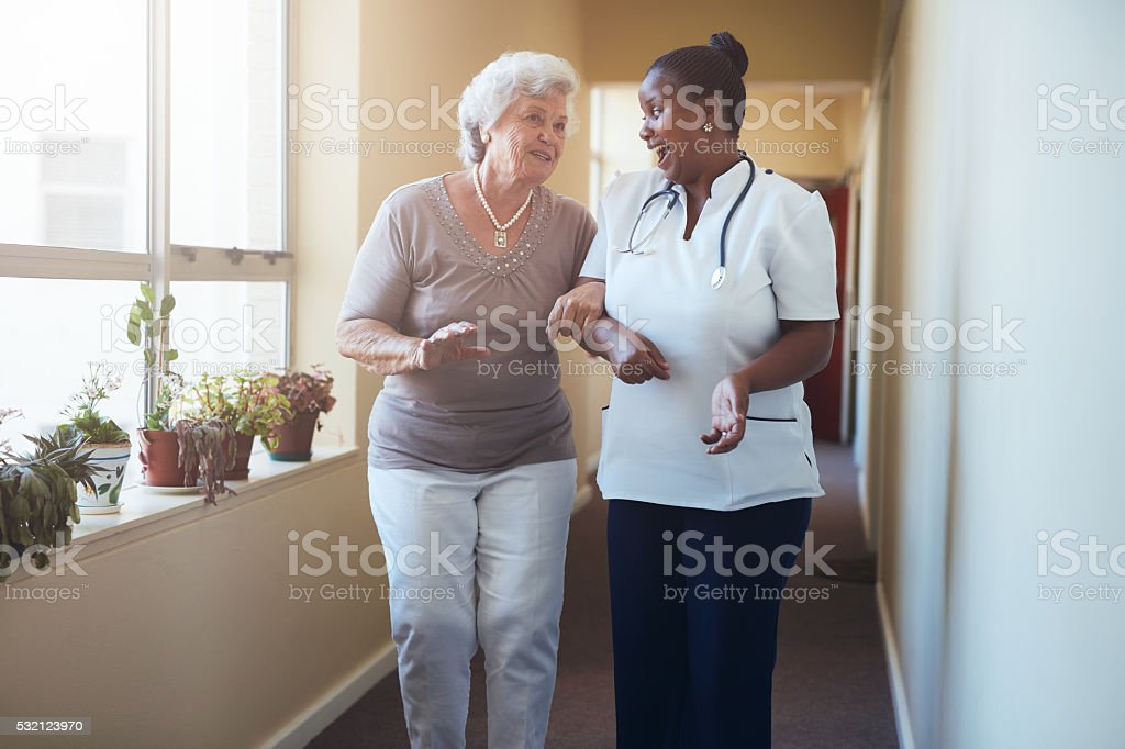Happy healthcare worker walking and talking with senior woman stock photo