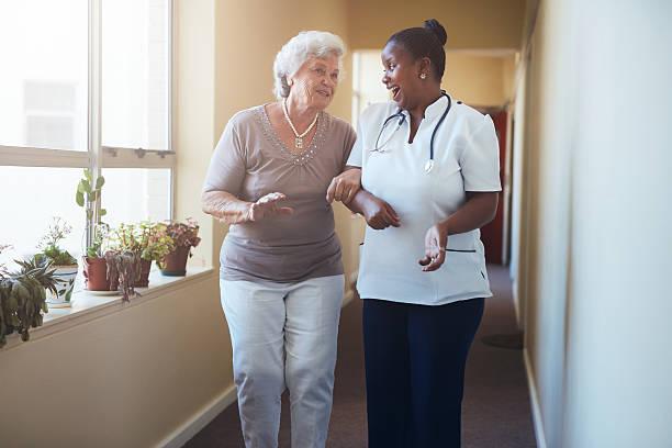 di personale sanitario a piedi e parlando con donna anziana - infermiera personale medico foto e immagini stock