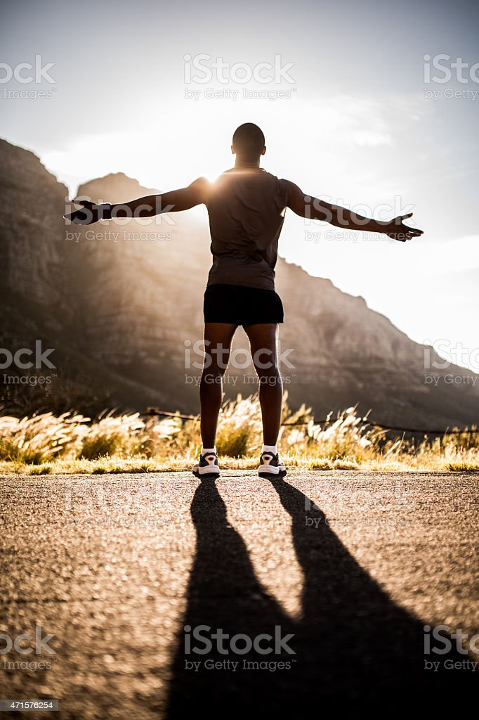 Happy healthy athlete appeciating the sun while on a run stock photo