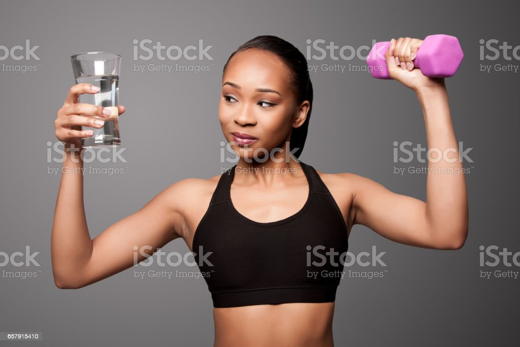 2e1729aa91b Happy healthy black asian woman with water and dumbbell royalty-free stock  photo