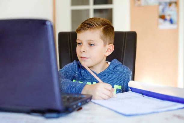 Glücklicher gesunder Junge mit Brille macht Schulhausaufgaben zu Hause mit Notebook. Interessierte Kind schreiben Essay mit Hilfe des Internets. Koncetiertes Schülerkonzept – Foto