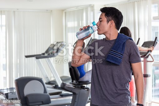 istock Happy healthy man are drinking water in the gym.After the exercise. 892876880
