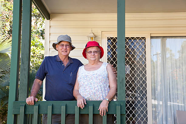 Happy Healthy Seniors Couple on porch in front of house stock photo