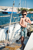 active healthy small kid in sunglasses and shorts standing on sea yacht board holding rope during summer travel holiday