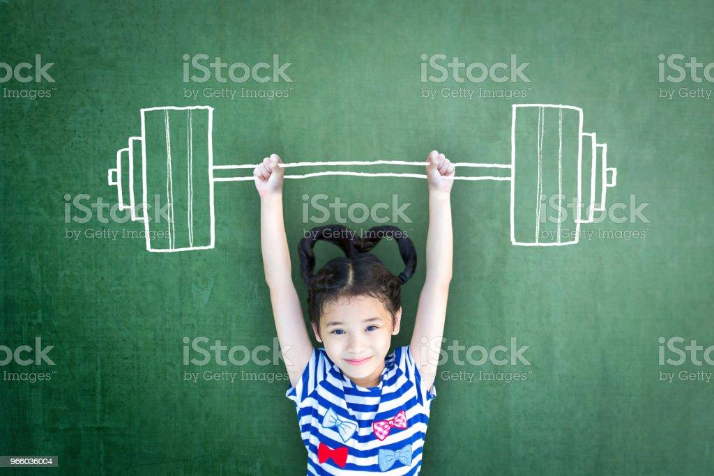 Glada friska starka kid styrketräning på grunge gröna svarta tavlan bakgrund: internationella dagen för flickor jämställdhet möjlighet medvetenhet på kvinnors mänskliga rättigheter barnens dag koncept ledare idé - Royaltyfri Asiatiskt och indiskt ursprung Bildbanksbilder