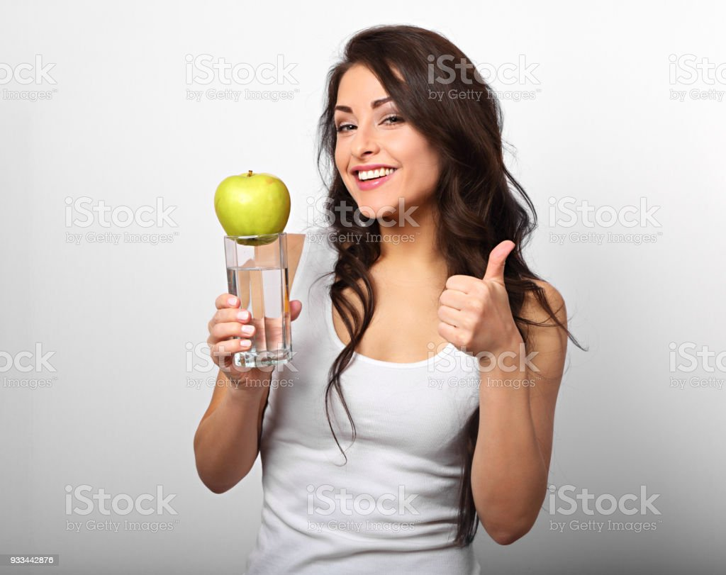 Happy healthy woman holding apple and clear water in hand, showing thumb up and looking with toothy smiling on white background stock photo