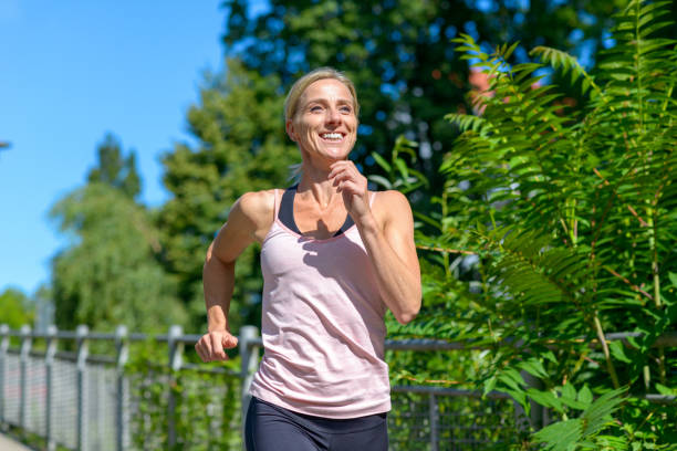 Happy healthy woman jogging outdoors stock photo