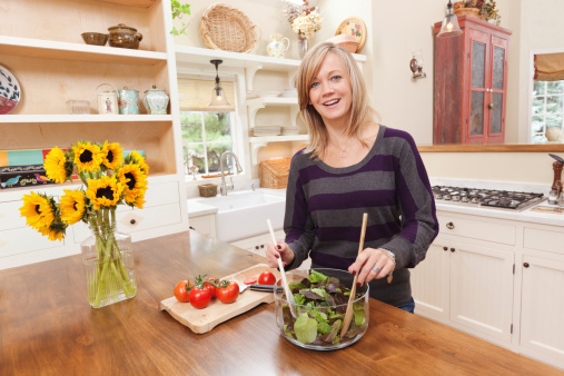 Happy Healthy Woman Preparing a Salad in Contemporary Home Kitchen