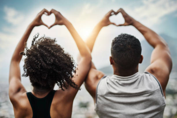 Happy hearts Rearview shot of a sporty young couple making heart shapes with their hands while exercising outdoors healthy heart stock pictures, royalty-free photos & images