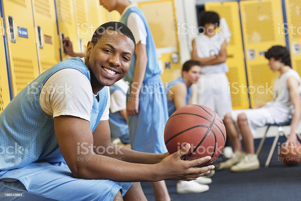 Happy high school basketball player in locker room after game stock photo