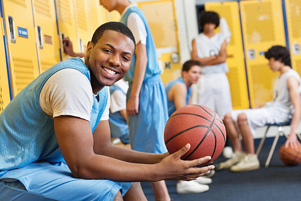 happy high school basketball player in locker room after game - high school sports stock photos and pictures