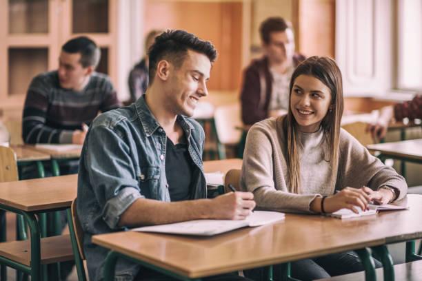 gelukkig middelbare schoolvrienden praten in de klas. - flirten stockfoto's en -beelden