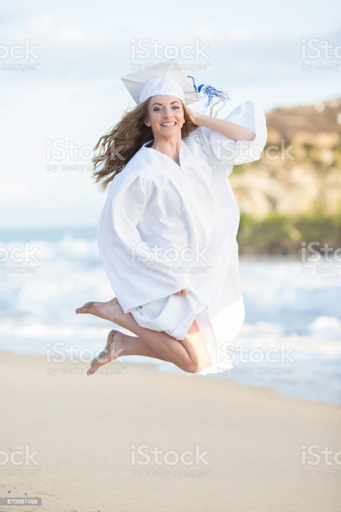 A happy high school graduate jumping at the beach stock photo