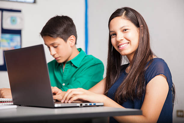 Happy high school student Beautiful Hispanic high school student using a laptop in a classroom cute middle school girls stock pictures, royalty-free photos & images