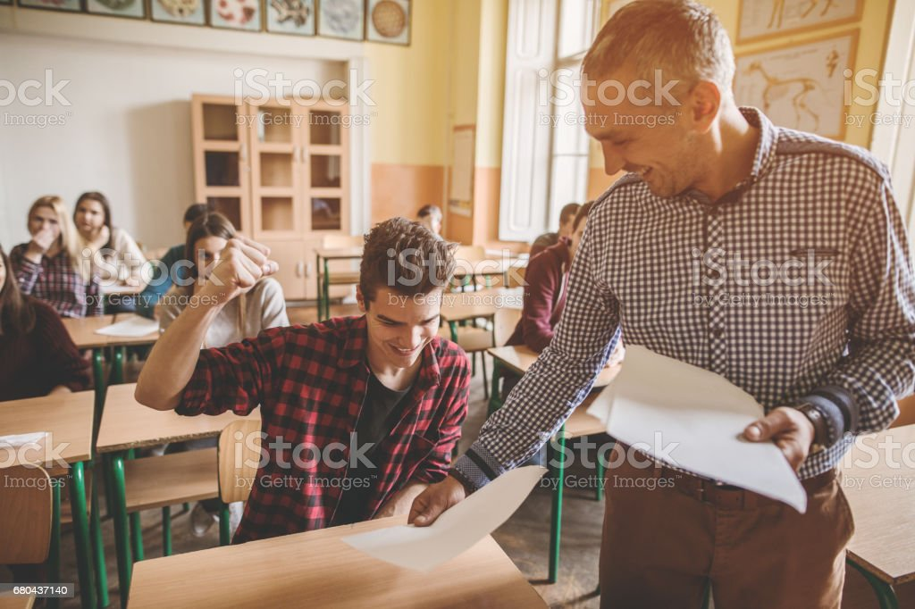 Happy high school student receiving exam results from the teacher. stock photo