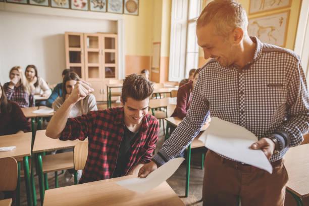estudante do colegial feliz receber exame resulta do professor. - happy test results - fotografias e filmes do acervo