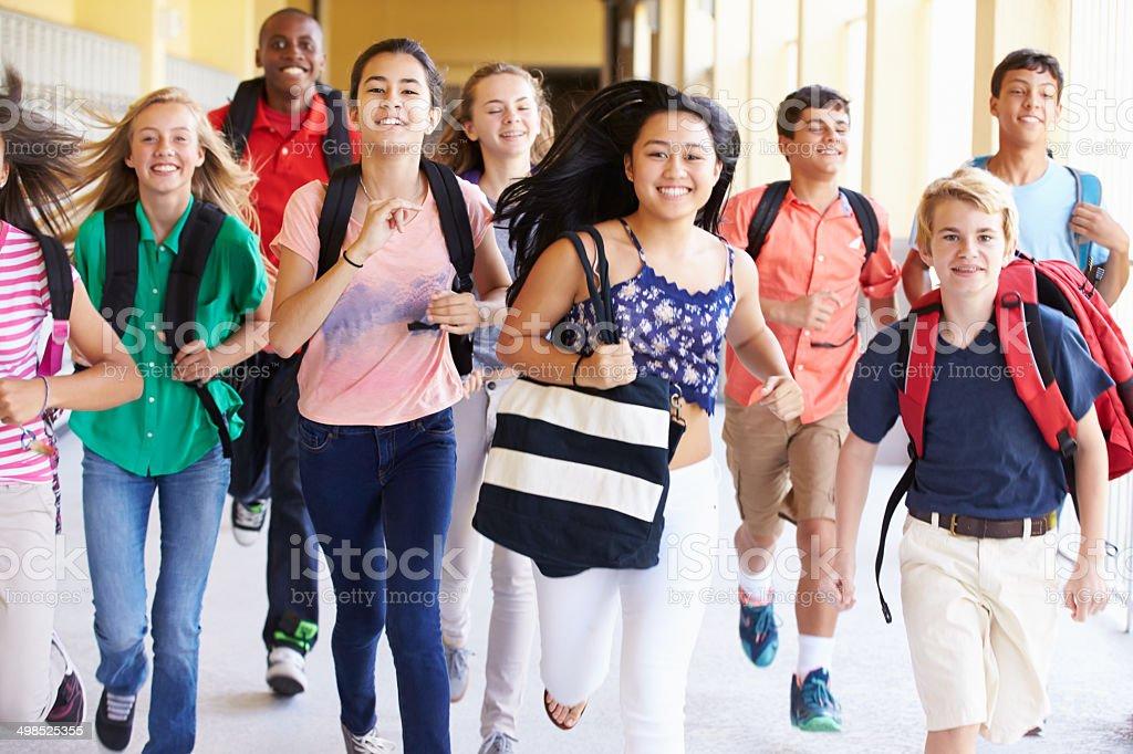Happy high school students running in hallway royalty-free stock photo