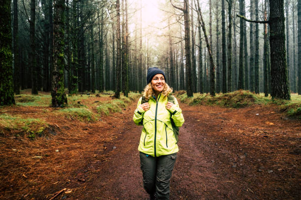 Happy hiker caucasian woman smile and enjoy the nature walking in a forest with high trees - alternative outdoor leisure activity and vacation lifestyle - sun in backlight and mist concept stock photo