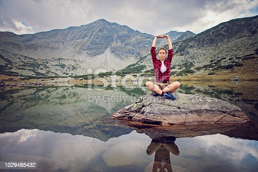 Happy hiker girl is practicing yoga in the mountain