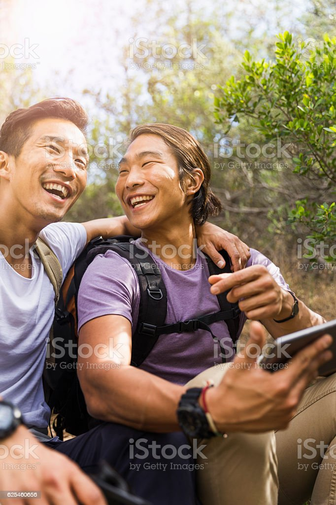 Happy hikers talking while using digital tablet royalty-free stock photo