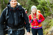 Man and woman hikers trekking in mountains. Young couple walking with backpacks in forest, Tatras in Poland. Trekking hiking outdoors in beautiful nature