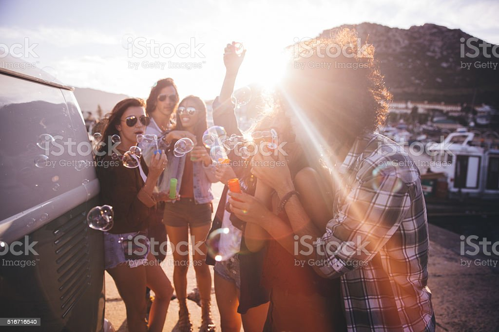 Happy hipster friend partying with bubbles outside at sunset stock photo