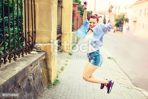 istock happy hipster girl jumping around urban landscape during music festival. 624703592