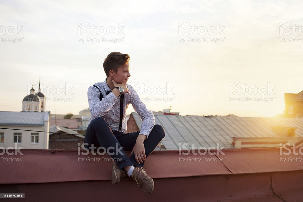 Happy hipster girl on the edge of the roof stock photo