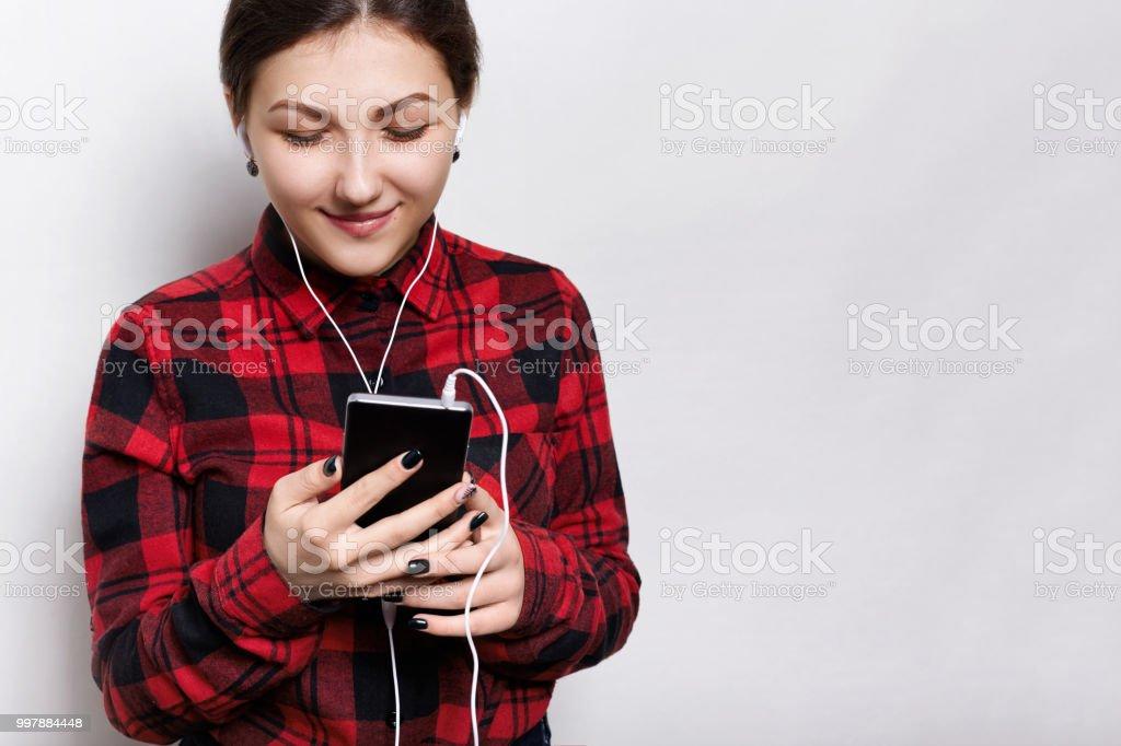 Garota de hipster feliz vestindo camisa vermelha segurando o smartphone nas mãos dela, ouvindo música ou audiobook com fones de ouvido, recebimento de mensagens de seu namorado feliz olhando para a tela de - foto de acervo