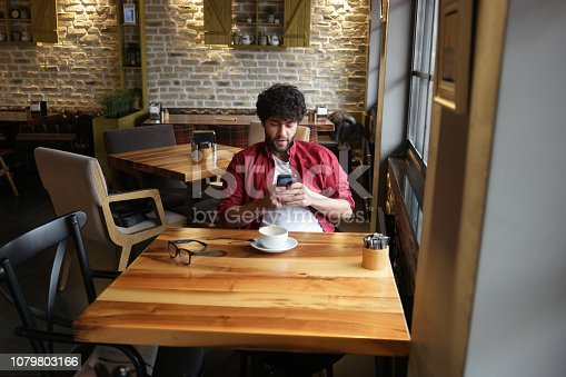824167622istockphoto Happy hipster man at coffee shop texting on mobile phone 1079803166